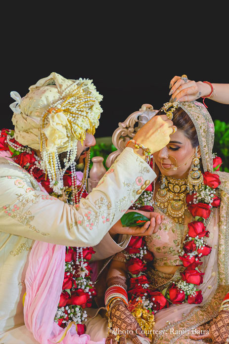 The bride wore a blush pink Sabyasachi lehenga with rich Polki and meenakari jewelry and groom wearing white, pink and gold sherwani for the wedding