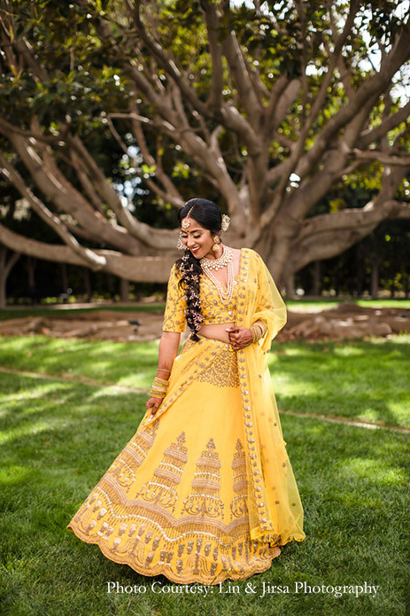 Bride wearing mustard yellow lehenga and groom wearing beige sherwani for the wedding at USA