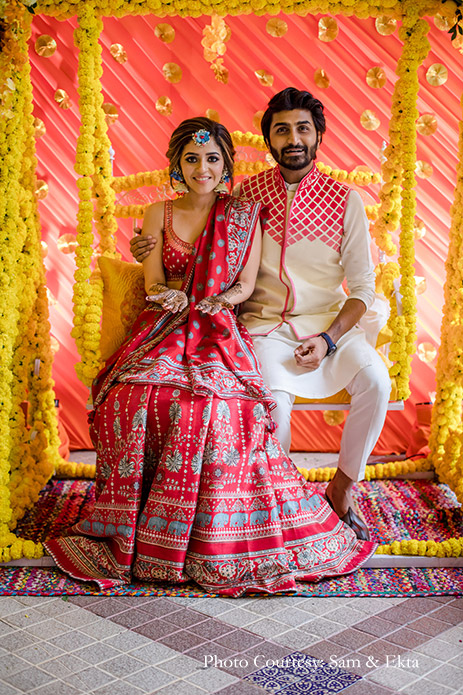 bride wore an Anita Dongre red and blue lehenga, accessorizing it with fresh floral jewelry in a soft braid decked with baby's breath and blue butterflies