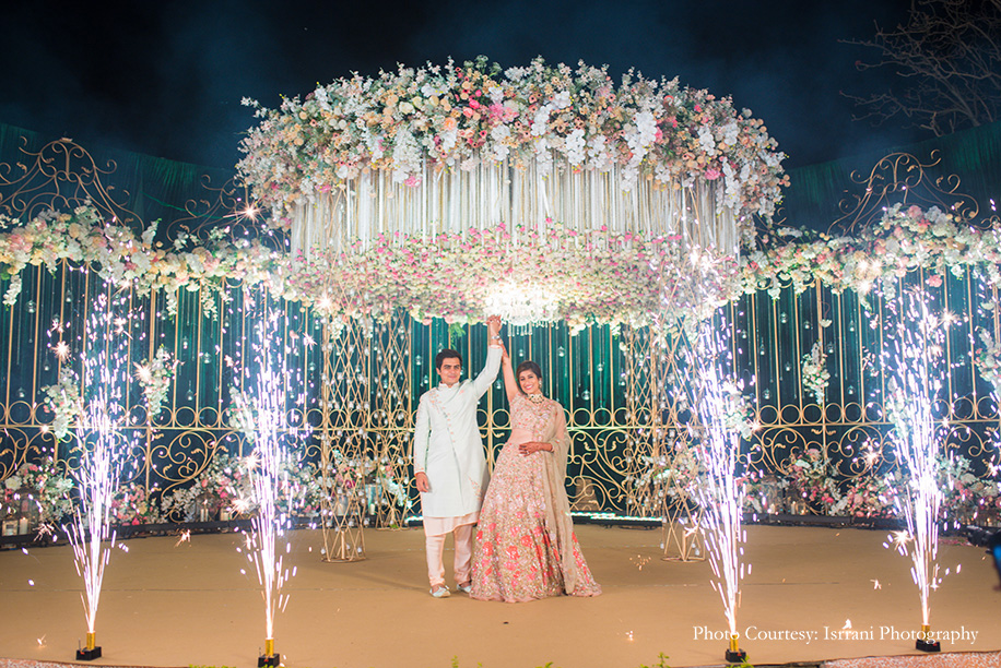 Bride in Beige and pink embroidered floral lehenga and Groom in pastel green bandhgala with pink floral embroidery details